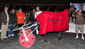 "In Your Eye, driven by Ridge Warren, worn the winning blanket of the Mike Paradise Series. He was joined in the winner's circle by the races honoree sporting his ""Illini Orange"" shirt and to his right was IHHA Director Joe Cassano."