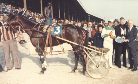 The late Robert F. Carey (right), general manager of Suburban Downs,  was in the winner's circle in 1974 to honor National Hall of Fame pacer Sir Dalrae and driver-trainer Jim Dennis. Note the sulky in those days was made of heavy wood. Also take notice of the jam-packed old open-air Grandstand at the old Hawthorne facility. (Hawthorne Photo)