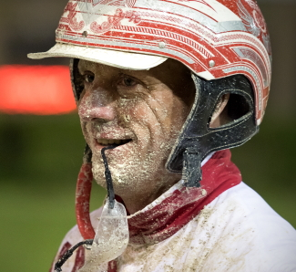 A muddy face and colors couldn't keep Matt Krueger from grinning from ear-to-ear after driving Phyllis Jean to her Open Pace victory. (Four Footed Fotos)