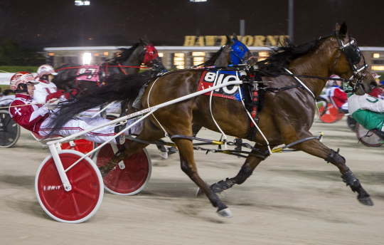 The Kim Roth Stable's Phyllis Jean (No. 10, Matt Krueger) is shown powering her way in the lane last Saturday in route to an upset victory in the $10,000 Open Pace for filly and mares. (Four Footed Fotos)