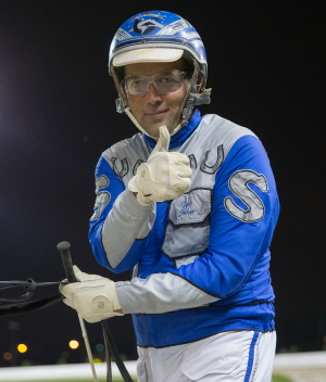 "Driver Tyler Shehan gave a ""thumbs up"" after steering Majistic Caprice to his victory in a second leg of the Erwin F. Dygert stake series. (Four Footed Fotos)"