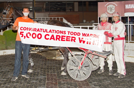 Todd Warren was joined in the Hawthorne winner's circle by his son Ridge and Hawthorne's Jim Miller after driving his 5,000 th career winner last night. (Four Footed Fotos)